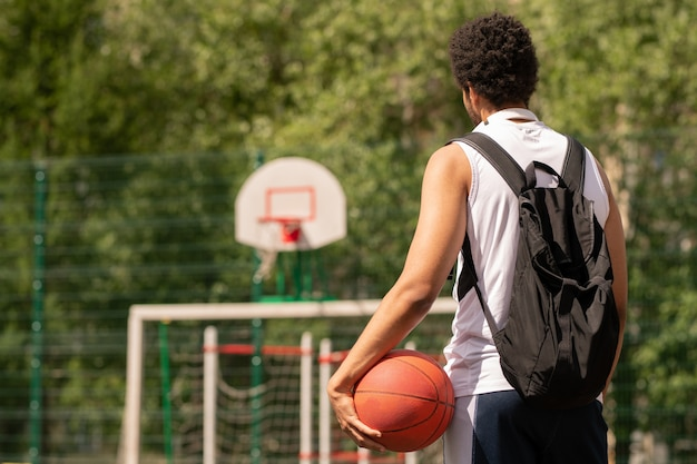 Jonge basketbalspeler met bal klaar voor spel staande op de rechtbank of speelplaats op zonnige dag