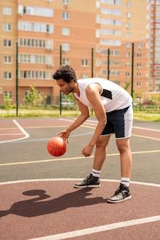 Jonge basketbalspeler oefenen met bal terwijl hij naar voren buigt over de rechtbank in stedelijke omgeving