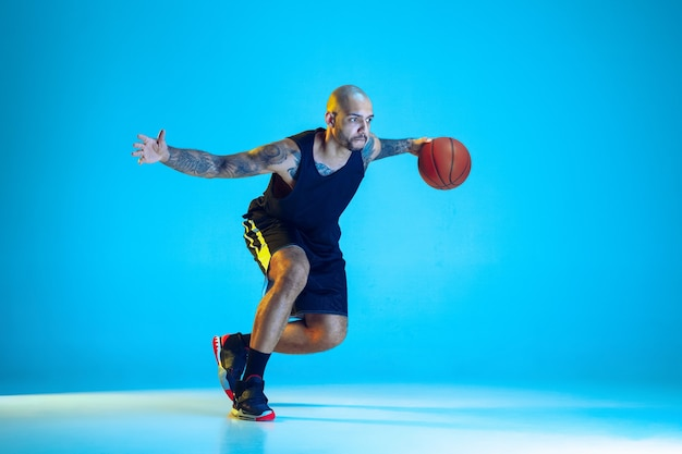 Jonge basketbalspeler van team draagt sportkleding training, oefenen in actie, geïsoleerd op blauwe muur in neonlicht