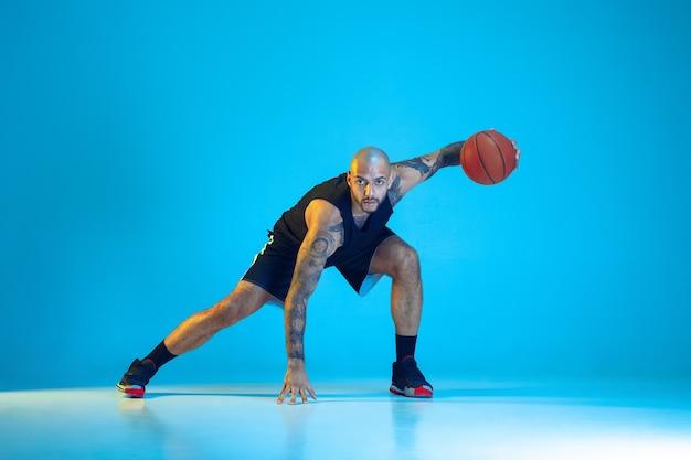 Jonge basketbalspeler van team dragen sportkleding training, oefenen in actie, beweging geïsoleerd op blauwe achtergrond in neonlicht. concept van sport, beweging, energie en dynamische, gezonde levensstijl.