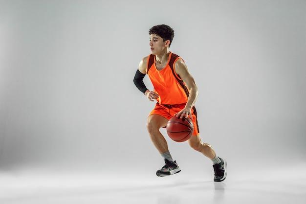 Jonge basketbalspeler van team dragen sportkleding training, oefenen in actie, beweging in run geïsoleerd op een witte muur. concept van sport, beweging, energie en dynamische, gezonde levensstijl.