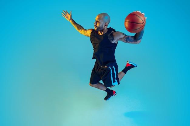 Jonge basketbalspeler van team dragen sportkleding training, oefenen in actie, beweging op blauwe muur in neonlicht