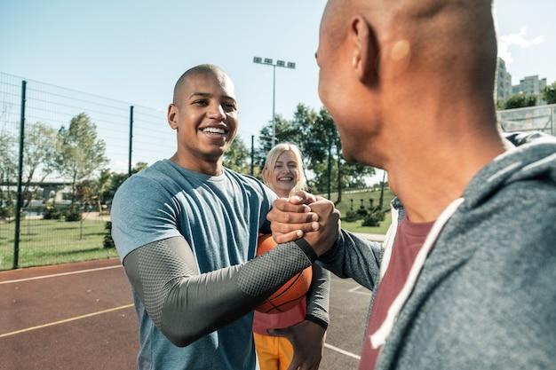 Jonge basketbalspelers. positieve jonge man die lacht terwijl hij naar zijn coach kijkt