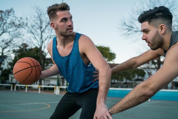 Jonge basketbalspelers spelen een-op-een.
