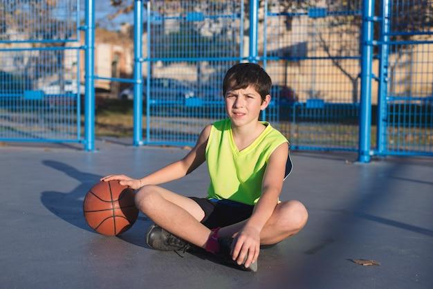 Jonge basketbalspelerzitting op het hof die gele mouwloos dragen