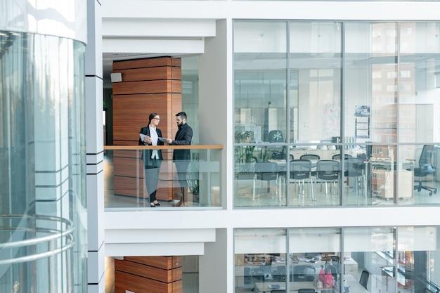 Jonge beambten die zich op balkon van commercieel centrum bevinden en ideeën voor nieuw project delen