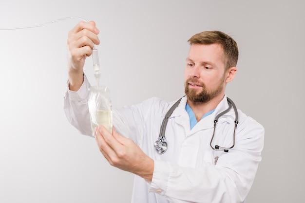 Jonge, bebaarde arts die met een stethoscoop transparante druppelaarzak met vloeibare geneeskunde houdt terwijl hij geïsoleerd voor de camera staat