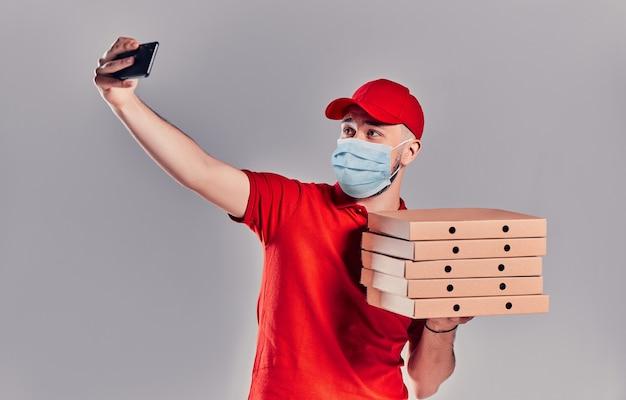 Jonge, bebaarde bezorger in een rood uniform en een beschermend medisch masker met pizzabodems maakt een selfie op een smartphone geïsoleerd op een grijze achtergrond.