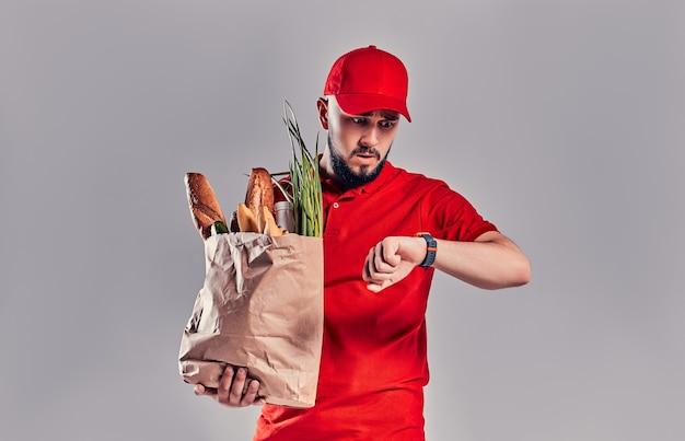 Jonge, bebaarde bezorger in een rood uniform houdt een pakket met brood en groenten vast en kijkt naar de smartwatch op zijn hand die laat is geïsoleerd op een grijze achtergrond.