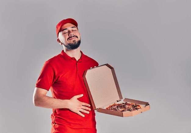 Jonge, bebaarde bezorger in een rood uniform met een doos pizza die zijn buik streelt en zijn ogen sluit, genietend van de geur van pizza geïsoleerd op een grijze achtergrond.