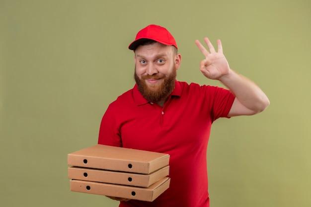Jonge, bebaarde bezorger in rood uniform en pet bedrijf stapel pizzadozen lachend met blij gezicht weergegeven: ok teken