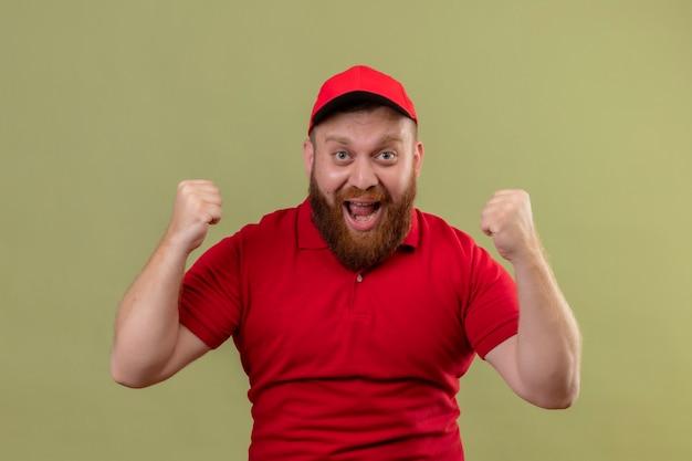 Jonge, bebaarde bezorger in rood uniform en pet, blij en opgewonden, gebalde vuisten verheugd over zijn succes
