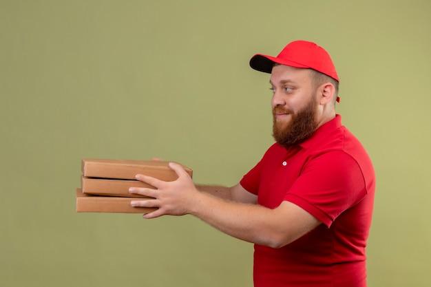 Jonge, bebaarde bezorger in rood uniform en pet die stapel pizzadozen geeft aan u klant vriendelijk lachend