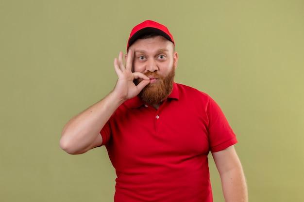 Jonge, bebaarde bezorger in rood uniform en pet die stilte gebaar maakt alsof hij zijn mond sluit met een rits