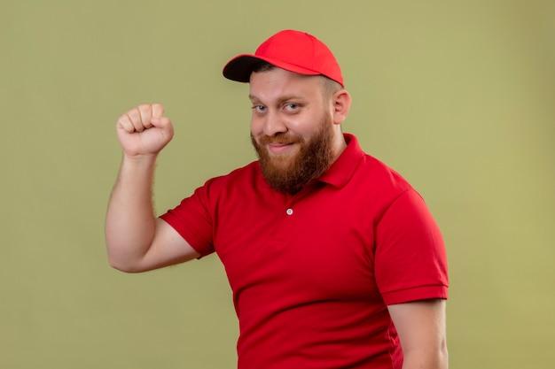 Jonge, bebaarde bezorger in rood uniform en pet glimlachend vriendelijk vuist heffen als winnaar, blij en positief 2