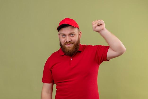 Jonge, bebaarde bezorger in rood uniform en pet glimlachend vriendelijk vuist heffen als winnaar, blij en positief