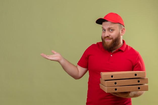 Jonge, bebaarde bezorger in rood uniform en pet met stapel pizzadozen die kopie ruimte met arm van zijn hand presenteren