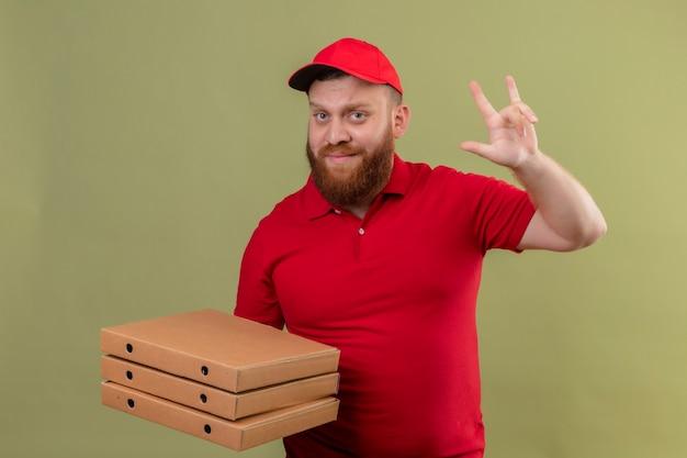 Jonge, bebaarde bezorger in rood uniform en pet met stapel pizzadozen die zelfverzekerd rotssymbool doen