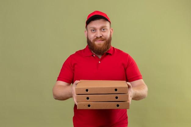 Jonge, bebaarde bezorger in rood uniform en pet met stapel pizzadozen glimlachend zelfverzekerd