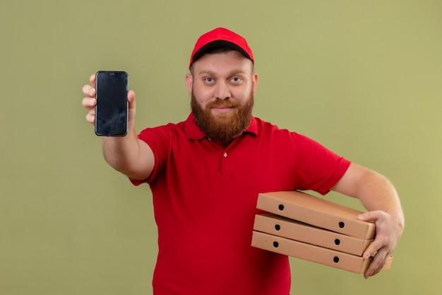 Jonge, bebaarde bezorger in rood uniform en pet met stapel pizzadozen smartphone tonen aan camera op zoek zelfverzekerd