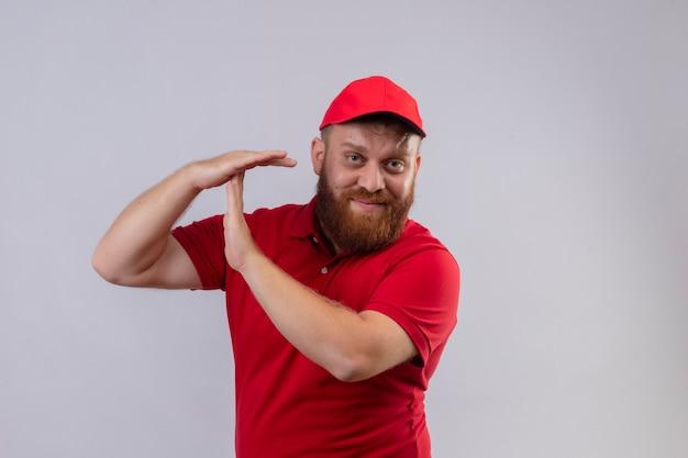 Jonge, bebaarde bezorger in rood uniform en pet op zoek moe en overwerkt waardoor time-out gebaar met handen