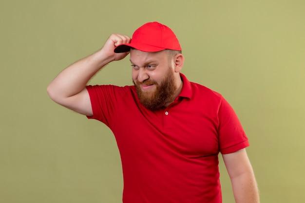 Jonge, bebaarde bezorger in rood uniform en pet op zoek verward en onzeker zijn hoofd krabben