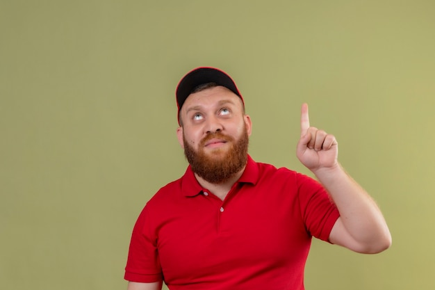 Jonge, bebaarde bezorger in rood uniform en pet opzoeken met wijsvinger omhoog met geweldig idee