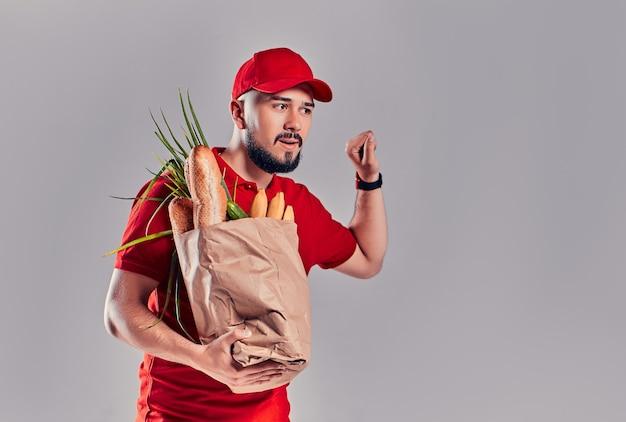 Jonge, bebaarde bezorger in rood uniform houdt een zak brood en groenten vast en klopt op een fictieve deur geïsoleerd op een grijze achtergrond.