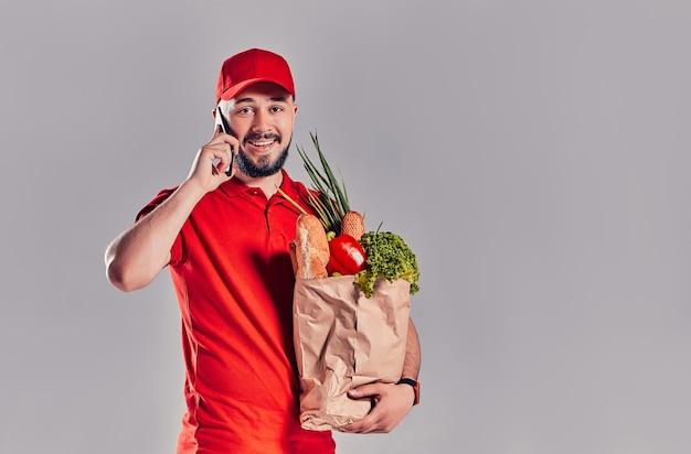 Jonge, bebaarde bezorger in rood uniform houdt pakket met brood en groenten en praat op smartphone geïsoleerd op een grijze achtergrond.