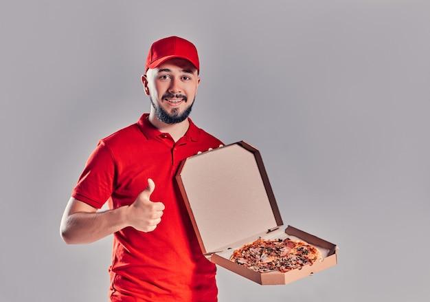 Jonge, bebaarde bezorger in rood uniform met pizza met duimen omhoog gebaar geïsoleerd op een grijze achtergrond.