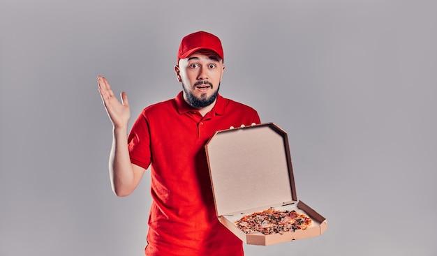 Jonge, bebaarde bezorger in rood uniform met pizzadoos geïsoleerd op een grijze achtergrond.
