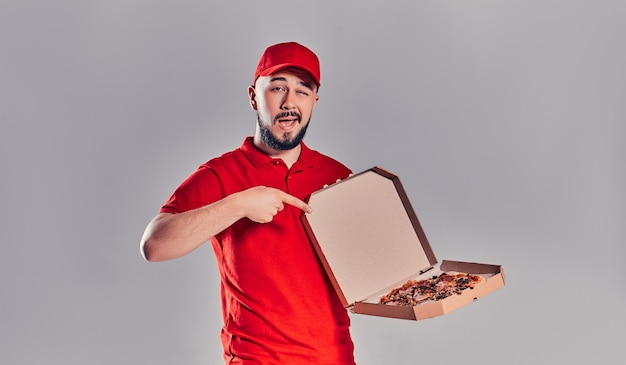 Jonge, bebaarde bezorger in rood uniform toont zijn vinger op pizzadoos geïsoleerd op een grijze achtergrond.