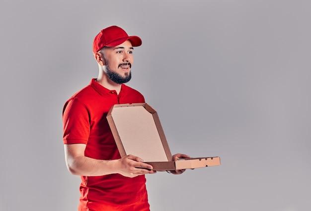 Jonge, bebaarde bezorger met pizzadoos geïsoleerd op een grijze achtergrond.