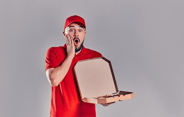 Jonge, bebaarde bezorger verrast geschokt in rood uniform met pizzadoos geïsoleerd op een grijze achtergrond.