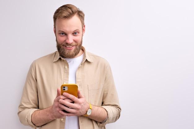 Jonge bebaarde blanke man chatten met iemand op smartphone, met een aangename glimlach