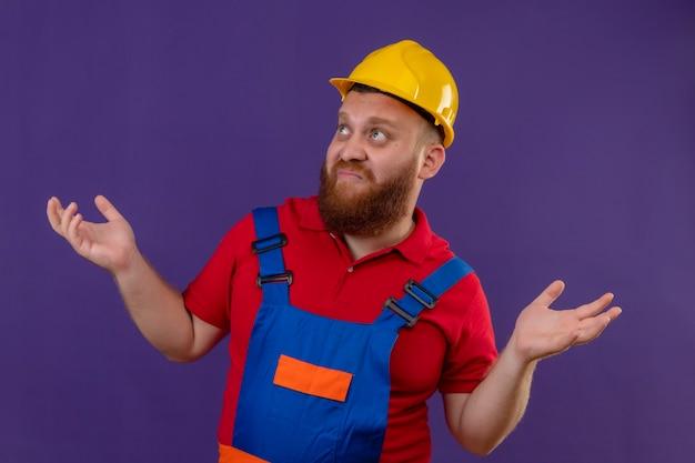 Jonge, bebaarde bouwer man in bouw uniform en veiligheidshelm op zoek verward schouderophalend schouders zonder antwoord, armen spreidend over paarse achtergrond