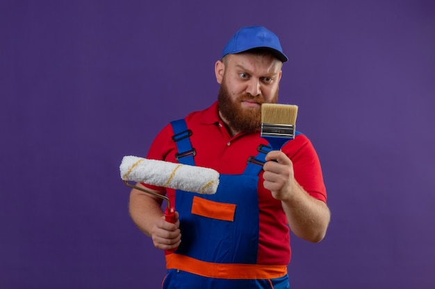Jonge, bebaarde bouwer man in uniform van de bouw en glb met verfroller en borstel kijken naar borstel met sceptische uitdrukking op gezicht op paarse achtergrond