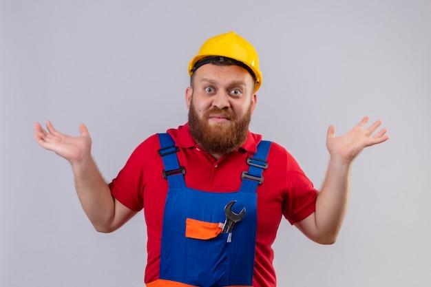 Jonge, bebaarde bouwersman in bouwuniform en veiligheidshelm die schouders ophaalt, er verward en onzeker uitziet, geen antwoord heeft, handpalmen spreidt