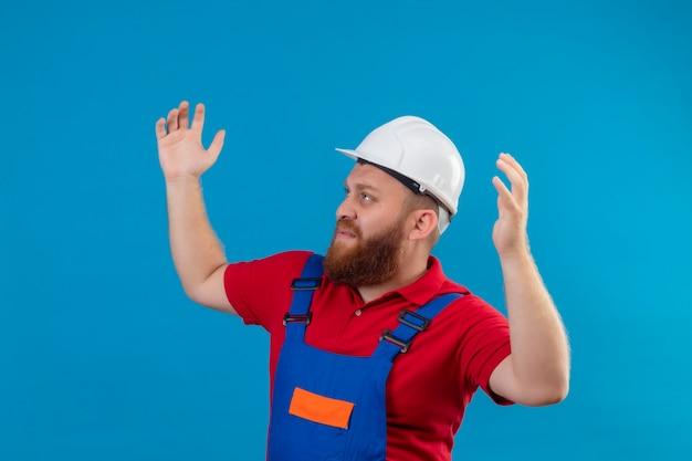 Jonge, bebaarde bouwersman in bouwuniform en veiligheidshelm die schouders ophaalt, er verward en onzeker uitziet, geen antwoord heeft, palmen spreidt