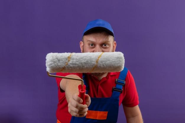 Jonge, bebaarde bouwersmens in bouwuniform en glb die zich uitstrekt naar camera verfroller over paarse achtergrond