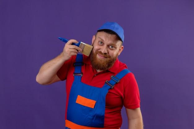 Jonge, bebaarde bouwersmens in bouwuniform en glb die zijn baard schilderen met een kwast glimlachend gelukkig en positief over purpere achtergrond