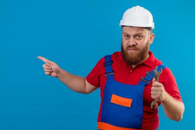 Jonge, bebaarde bouwersmens in bouwuniform en moersleutel van de veiligheidshelmholding ontevreden wijzend met wijsvinger naar de zijkant