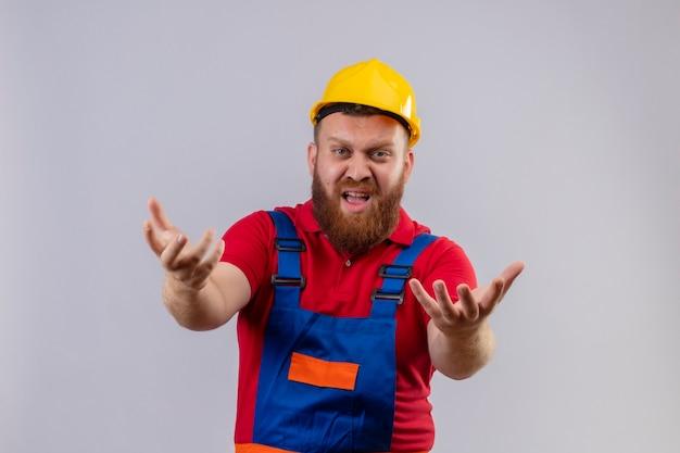 Jonge, bebaarde bouwersmens in bouwuniform en veiligheidshelm boos en gefrustreerd schreeuwen met opgeheven armen
