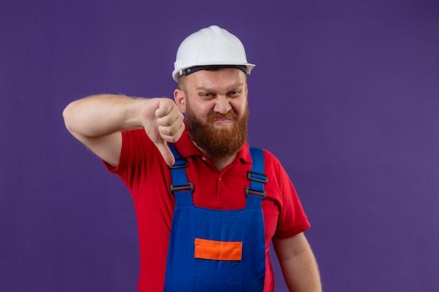 Jonge, bebaarde bouwersmens in bouwuniform en veiligheidshelm die afkeer met ontevreden gezicht tonen die duimen neer over purpere achtergrond tonen