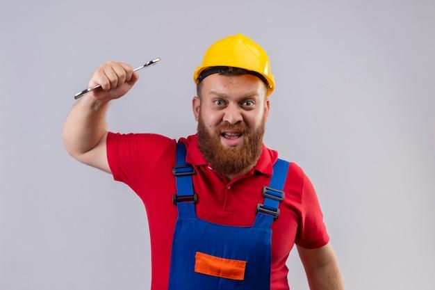Jonge, bebaarde bouwersmens in bouwuniform en veiligheidshelm die een moersleutel met agressieve uitdrukking slingeren