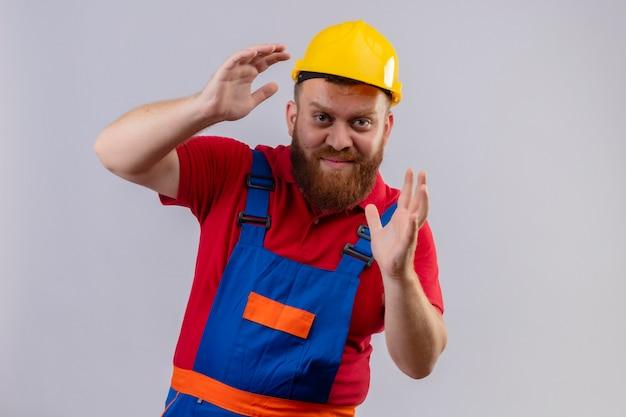 Jonge, bebaarde bouwersmens in bouwuniform en veiligheidshelm die groottegebaar met handen met zelfverzekerde glimlach op gezicht, maatregelen symbool tonen