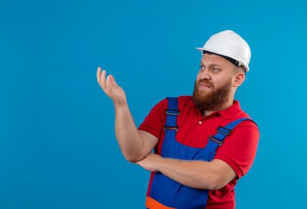 Jonge, bebaarde bouwersmens in bouwuniform en veiligheidshelm die opzij ontevreden met opgeheven hand kijken