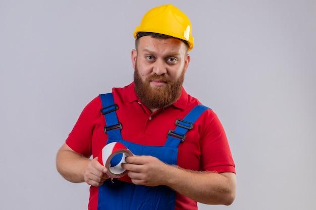 Jonge, bebaarde bouwersmens in bouwuniform en veiligheidshelm die plakband houden die camera met ernstig gezicht bekijken