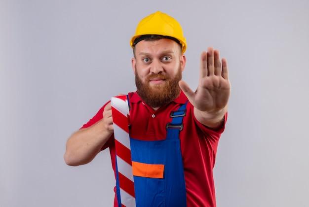 Jonge, bebaarde bouwersmens in bouwuniform en veiligheidshelm die plakband houden die zich met open hand bevinden die stopbord maken op witte achtergrond