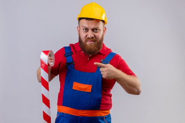 Jonge, bebaarde bouwersmens in bouwuniform en veiligheidshelm die plakband houdt die met vinger ernaar richt op zoek ontevreden